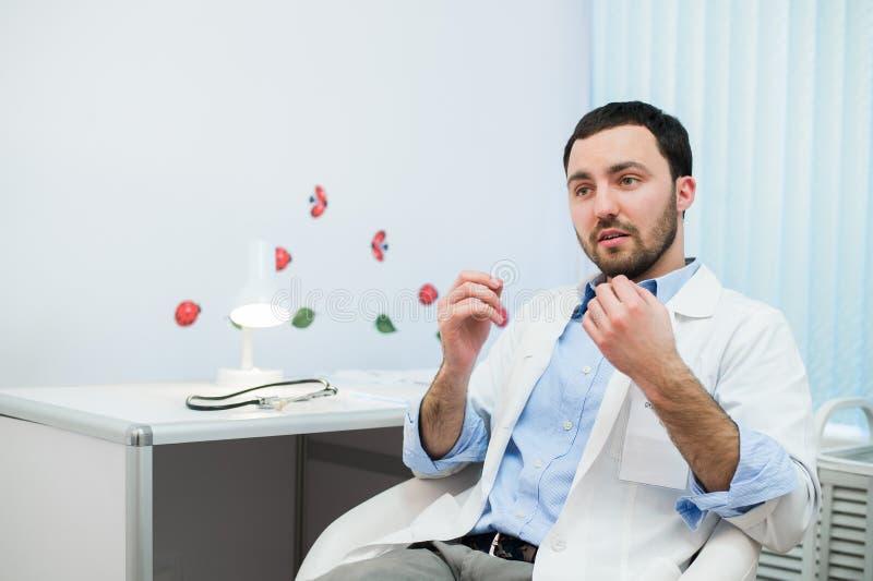 Doctor de sexo masculino amistoso del terapeuta de la medicina que se sienta en oficina, el hablar paciente y mirada a la cámara  foto de archivo