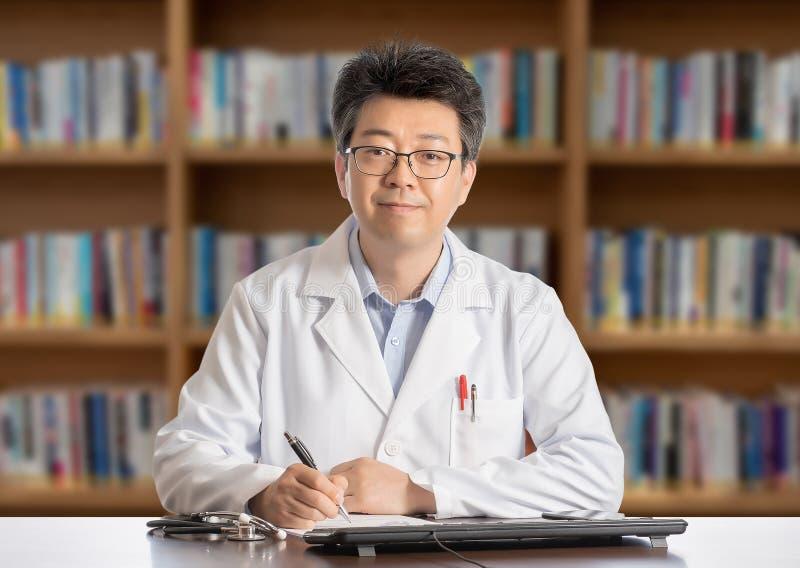 Doctor de sexo masculino asiático que se sienta en la sonrisa del escritorio foto de archivo