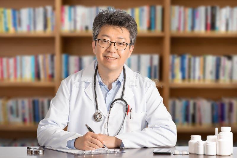 Doctor de sexo masculino asiático que se sienta en la sonrisa del escritorio imagenes de archivo
