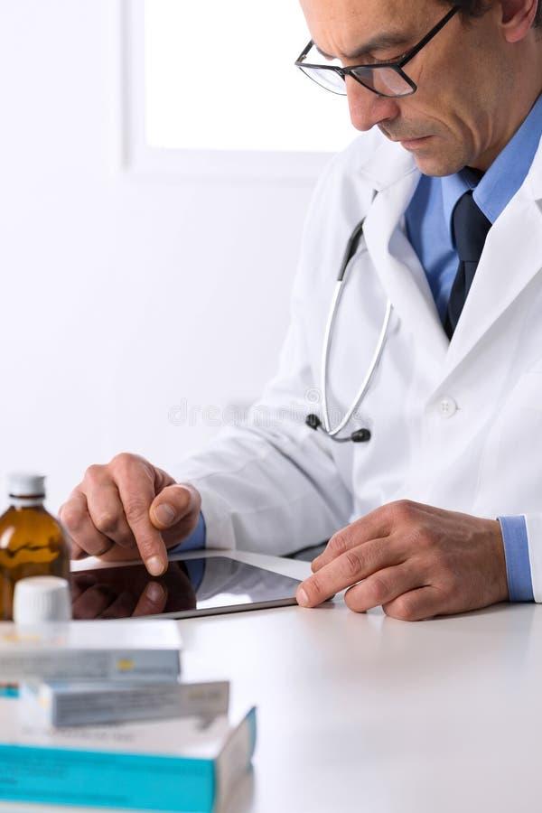 Doctor de sexo masculino con el estetoscopio en el escritorio usando la tableta fotografía de archivo
