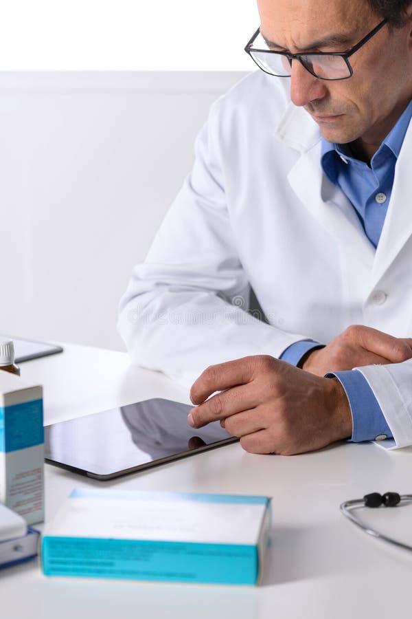 Doctor de sexo masculino con el estetoscopio en el escritorio usando la tableta fotografía de archivo libre de regalías