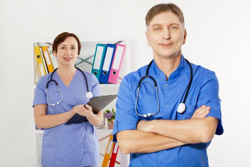 Doctor de sexo masculino con los brazos cruzados y doctor de sexo femenino con la carpeta en la oficina m?dica, seguro m?dico, es imagenes de archivo