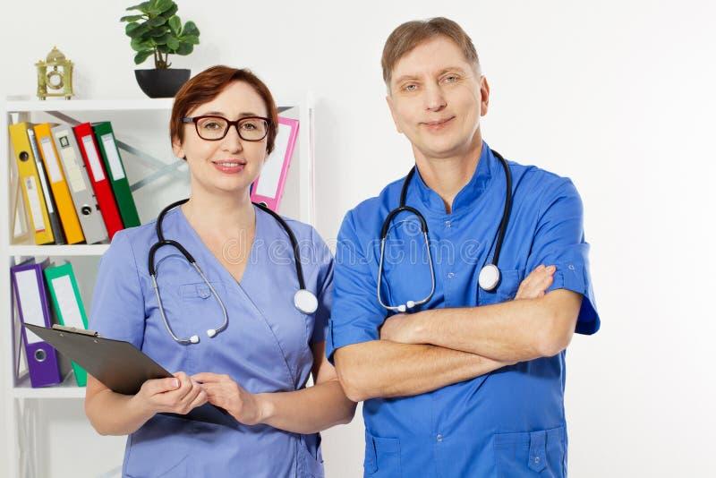 Doctor de sexo masculino con los brazos cruzados y doctor de sexo femenino con la carpeta en la oficina m?dica, seguro m?dico, es fotos de archivo libres de regalías