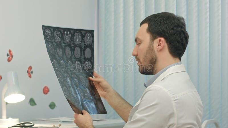 Doctor de sexo masculino concentrado que mira la imagen de la radiografía en la oficina médica foto de archivo libre de regalías