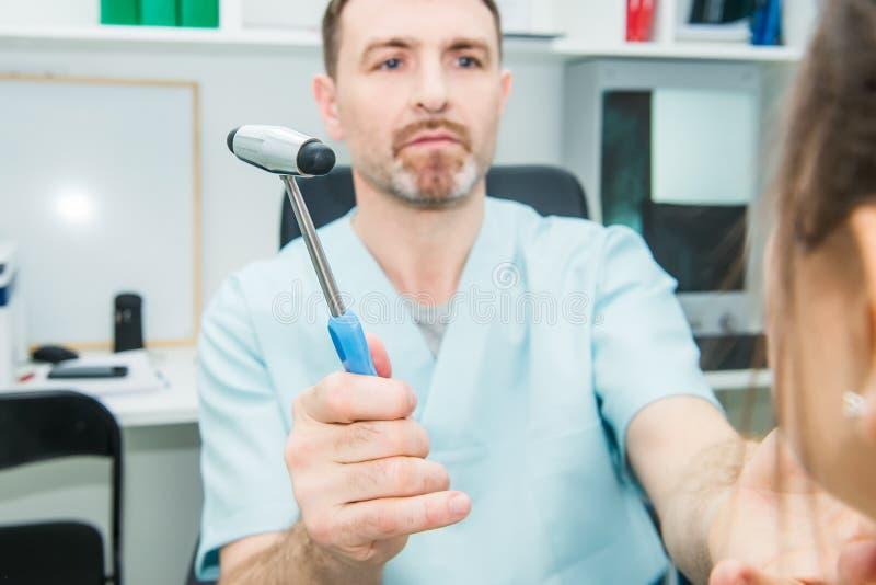 Doctor de sexo masculino del neurólogo que examina el sistema nervioso paciente femenino joven del ` s usando un martillo Examen  fotografía de archivo libre de regalías