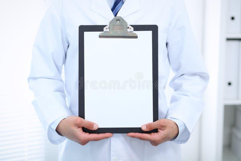 Doctor de sexo masculino desconocido que se coloca recto mientras que sostiene el tablero médico con el Libro Blanco en blanco Me imágenes de archivo libres de regalías