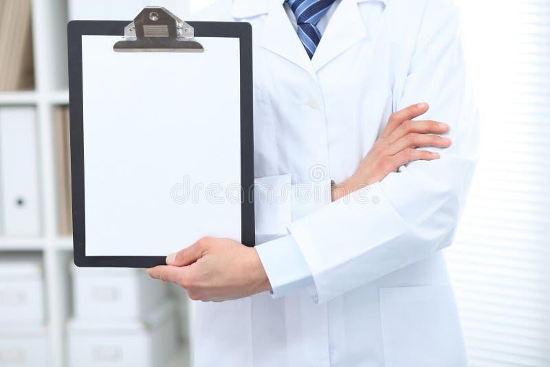 Doctor de sexo masculino desconocido que se coloca recto mientras que sostiene el tablero médico con el Libro Blanco en blanco Me fotos de archivo libres de regalías