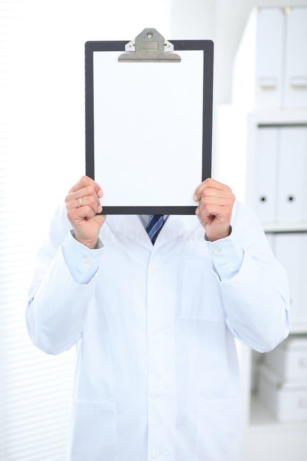 Doctor de sexo masculino desconocido que se coloca recto mientras que sostiene el tablero médico con el Libro Blanco en blanco en imagenes de archivo