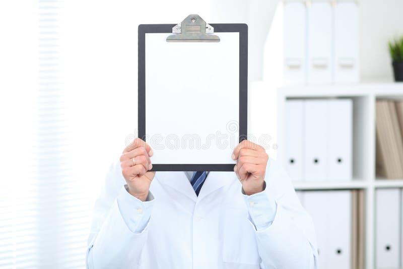 Doctor de sexo masculino desconocido que se coloca recto mientras que sostiene el tablero médico con el Libro Blanco en blanco en imagen de archivo libre de regalías