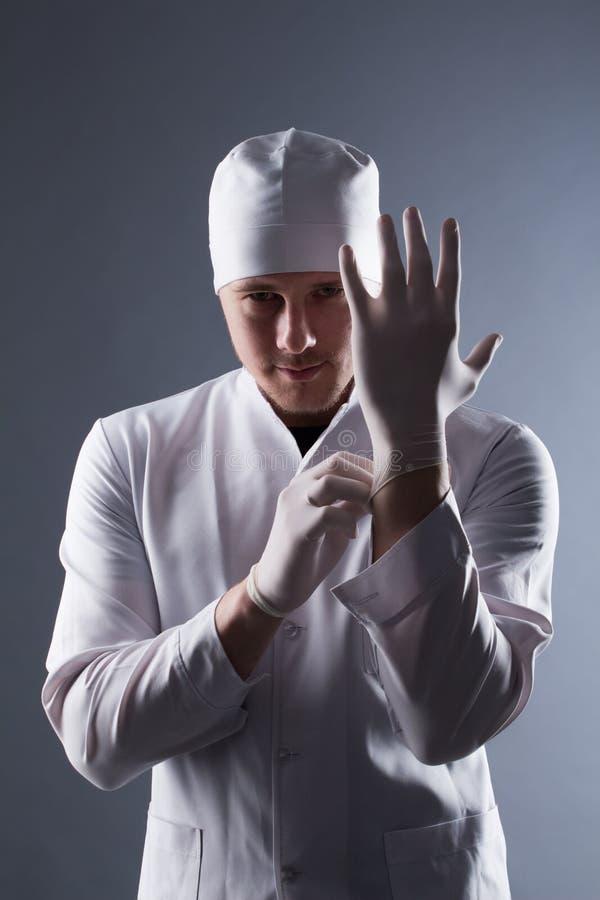 Doctor de sexo masculino en casquillo con los guantes médicos de goma del desgaste de la barba en el cont imagenes de archivo