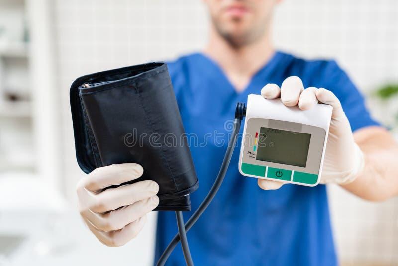 Doctor de sexo masculino en el monitor uniforme azul de la presión arterial que se sostiene, primer Objeto m?dico foto de archivo