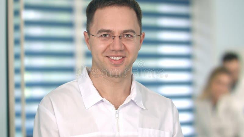 Doctor de sexo masculino en vidrios que sonríe en la cámara mientras que personal médico que trabaja en el fondo fotos de archivo
