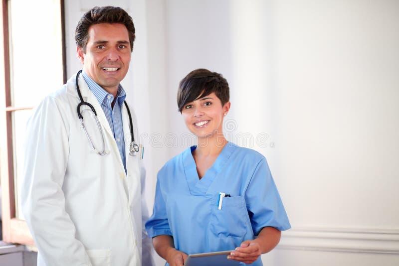 Doctor de sexo masculino encantador y situación bonita de la enfermera foto de archivo