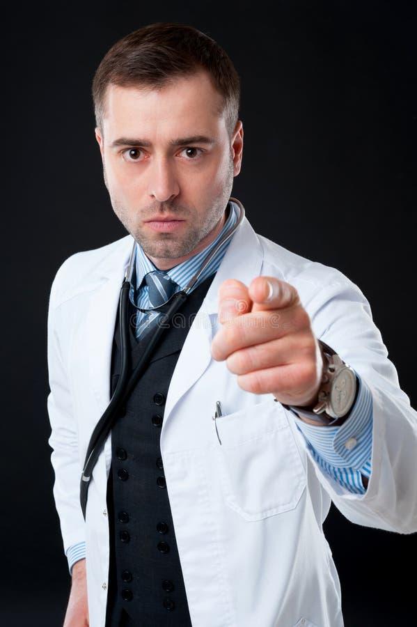 Doctor de sexo masculino enojado que señala en usted imagenes de archivo
