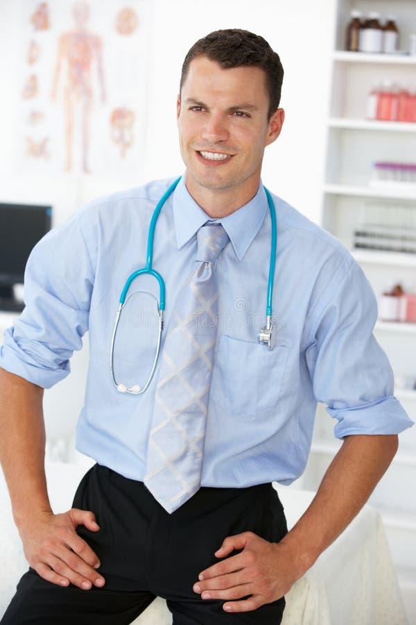 Doctor de sexo masculino feliz en sitio de consulta imagen de archivo
