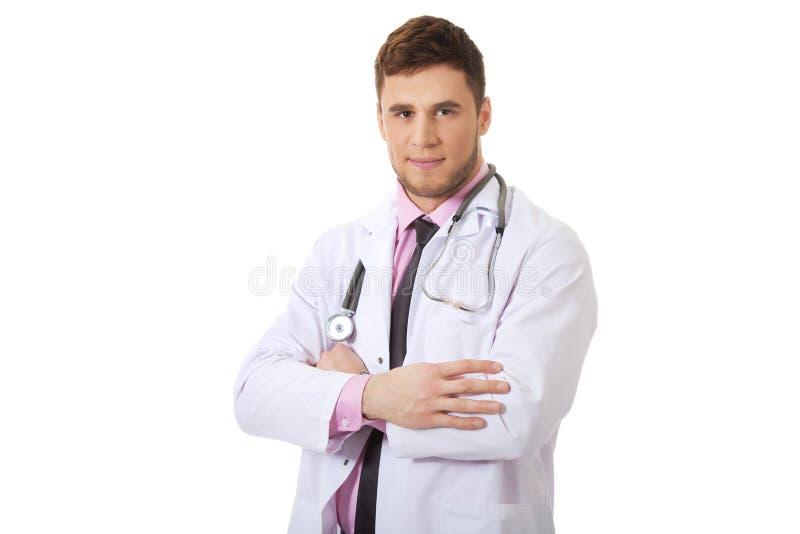 Doctor de sexo masculino feliz joven con los brazos doblados imagen de archivo libre de regalías