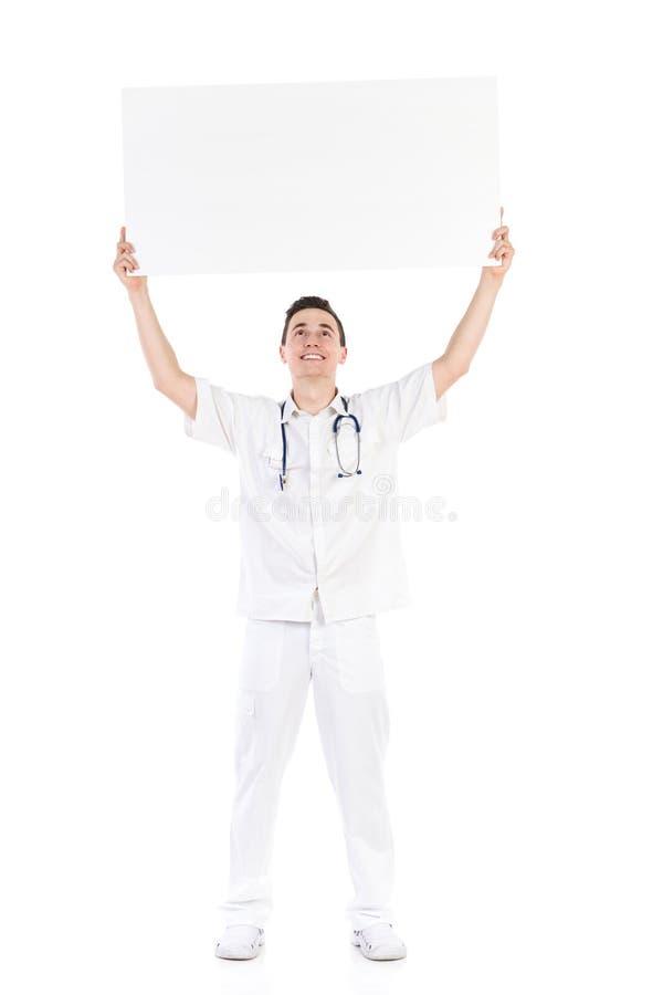 Doctor de sexo masculino feliz que lleva a cabo el cartel vacío sobre su cabeza foto de archivo libre de regalías