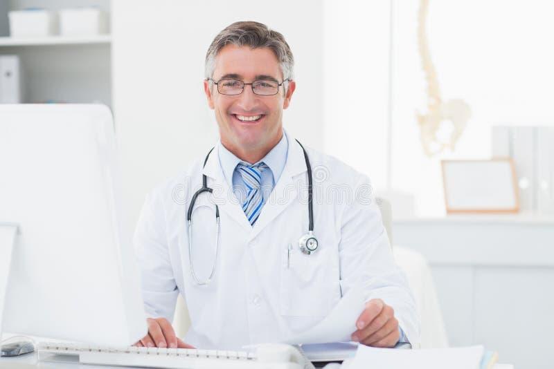 Doctor de sexo masculino feliz que revisa documentos en la tabla foto de archivo libre de regalías