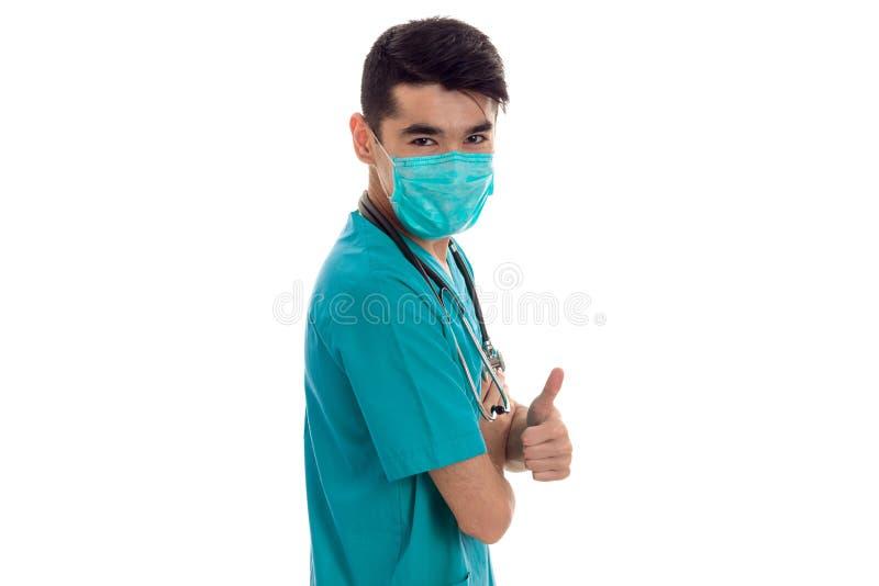 Doctor de sexo masculino hermoso en uniforme y máscara con el estetoscopio en su cuello que mira la cámara y que muestra los pulg imagenes de archivo