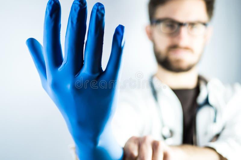 Doctor de sexo masculino joven con el guante azul imagenes de archivo