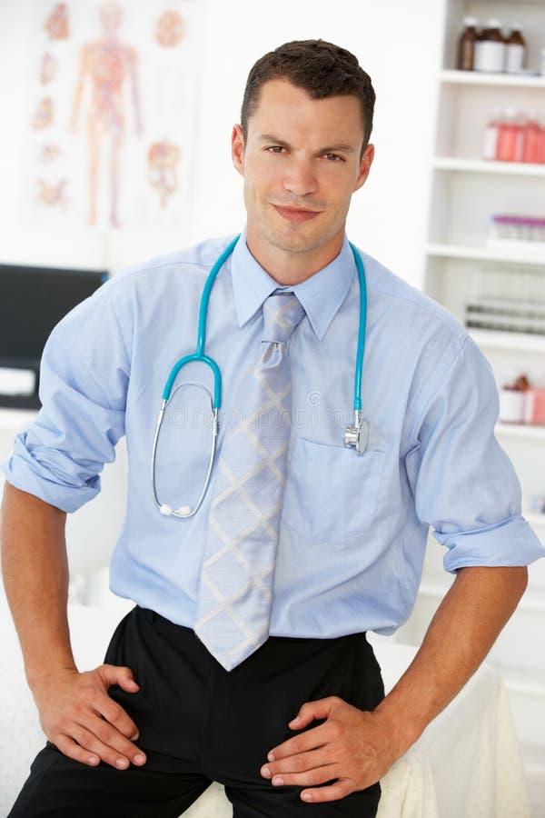 Doctor de sexo masculino joven en sitio de consulta imagen de archivo