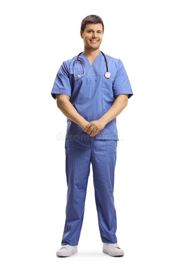 Doctor de sexo masculino joven en un uniforme azul que presenta y que sonríe fotos de archivo libres de regalías