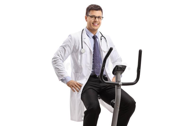 Doctor de sexo masculino joven en una bici inmóvil que mira la cámara y la sonrisa fotos de archivo libres de regalías