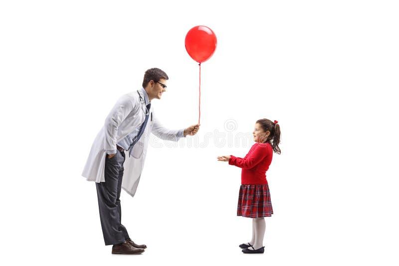 Doctor de sexo masculino joven que da un globo rojo a una niña imagen de archivo libre de regalías