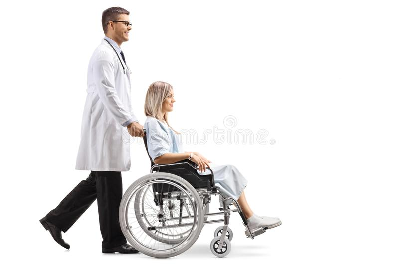 Doctor de sexo masculino joven que empuja a un paciente femenino en una silla de ruedas foto de archivo libre de regalías