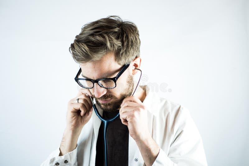 Doctor de sexo masculino joven que pone en un estetoscopio fotografía de archivo libre de regalías