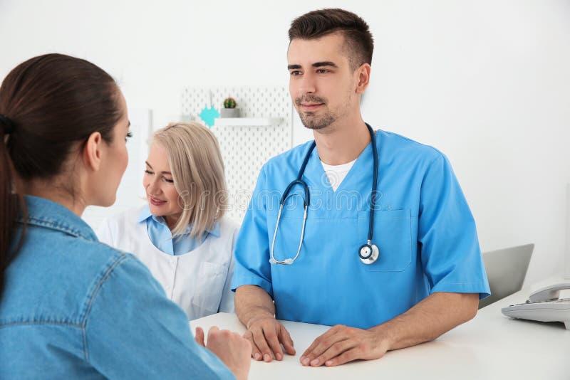 Doctor de sexo masculino joven y recepcionista de sexo femenino mayor foto de archivo libre de regalías