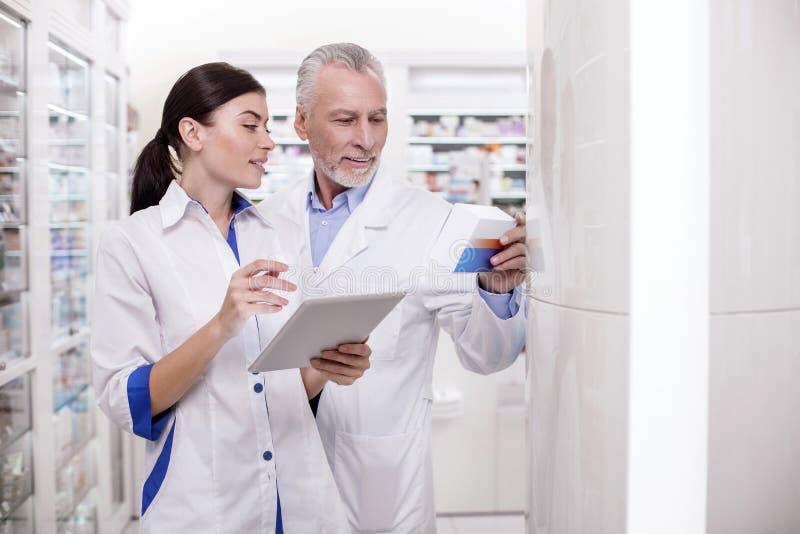 Doctor de sexo masculino maduro que ayuda al farmacéutico fotografía de archivo