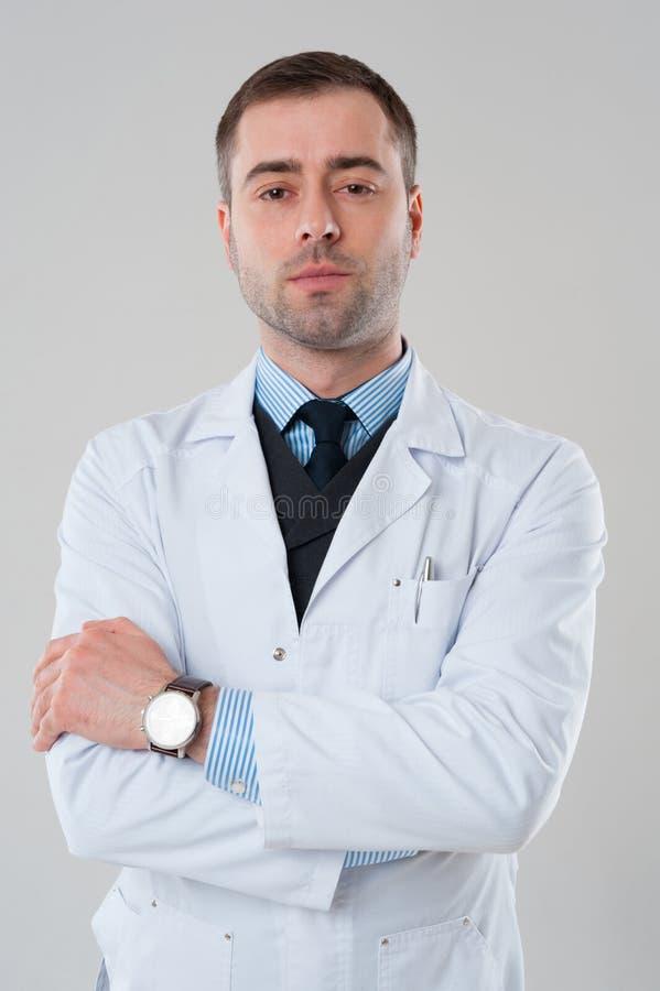 Doctor de sexo masculino maduro sonriente con los brazos cruzados aislados en vagos grises fotos de archivo