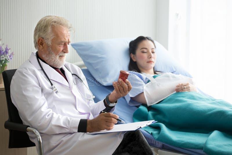 Doctor de sexo masculino mayor que comprueba las botellas marrones de la medicina de mujer paciente joven en cama de hospital fotos de archivo