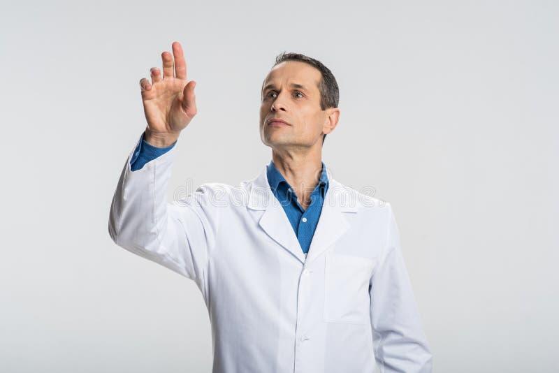 Doctor de sexo masculino pensativo que estima ocasiones fotos de archivo libres de regalías