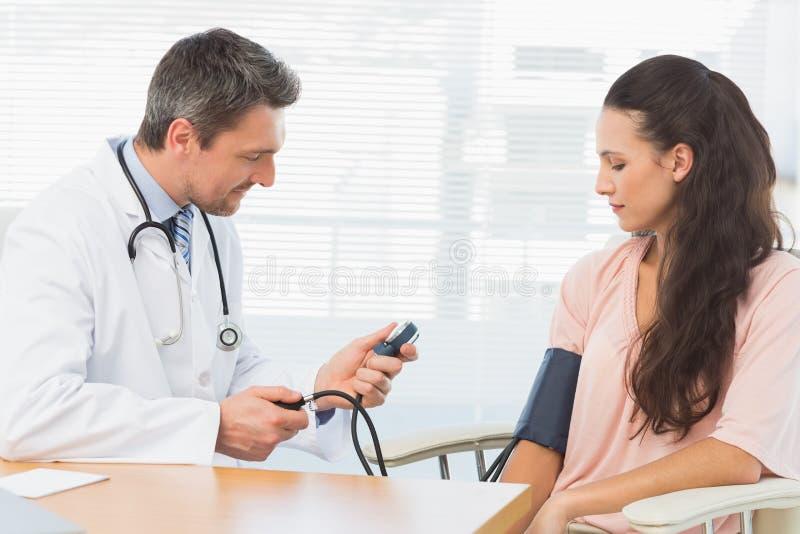 Doctor de sexo masculino que comprueba la presión arterial de una mujer imagen de archivo libre de regalías