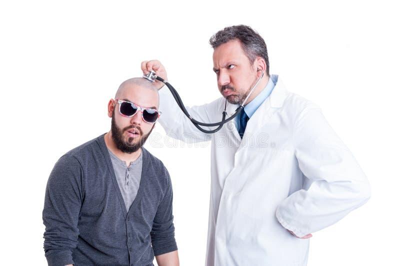 Doctor de sexo masculino que consulta a un paciente loco con el estetoscopio fotografía de archivo libre de regalías