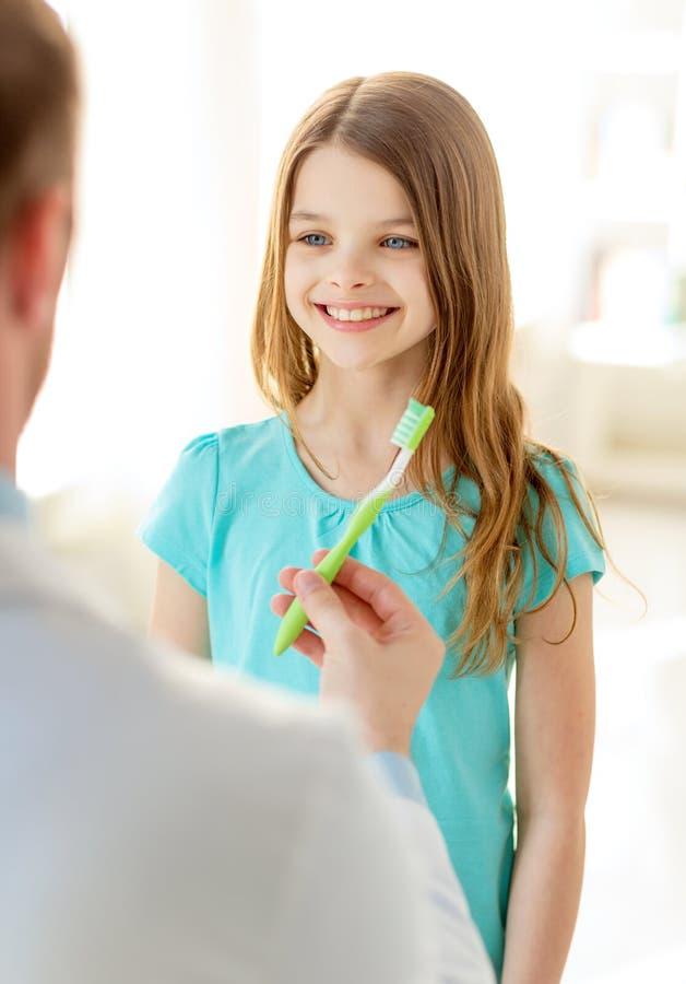 Doctor de sexo masculino que da el cepillo de dientes a la muchacha sonriente foto de archivo libre de regalías