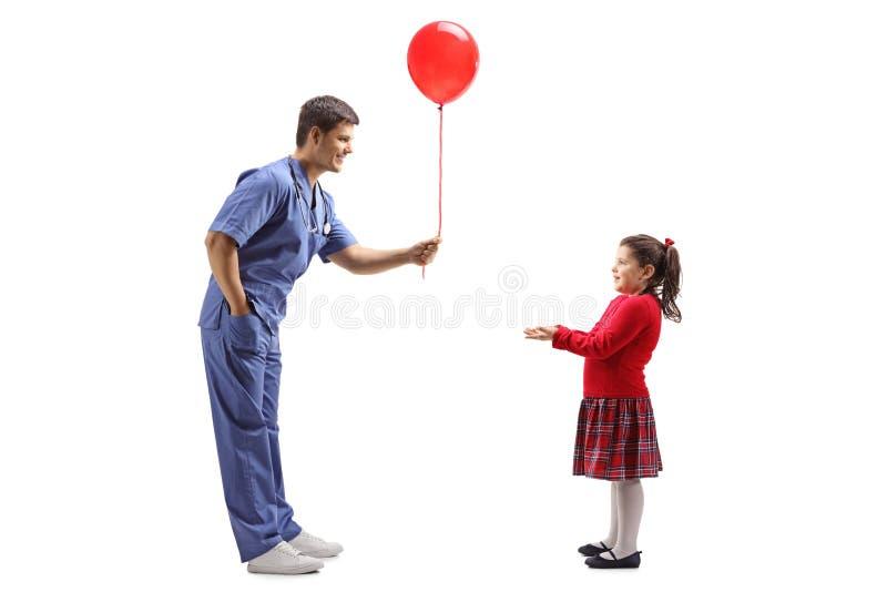 Doctor de sexo masculino que da un globo rojo a una niña foto de archivo libre de regalías