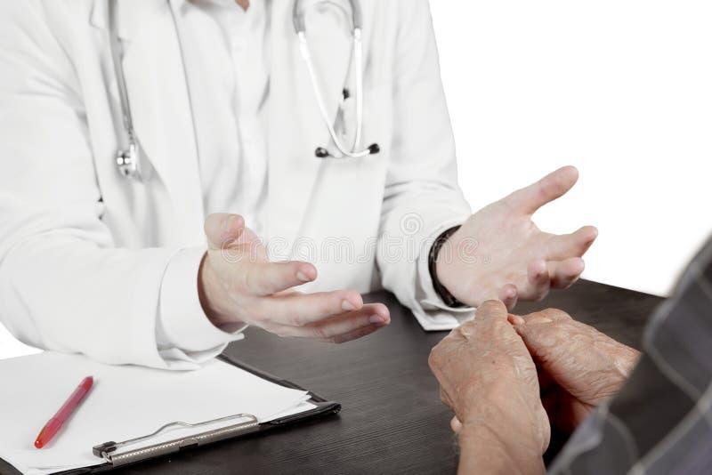 Doctor de sexo masculino que discute con su paciente mayor fotografía de archivo