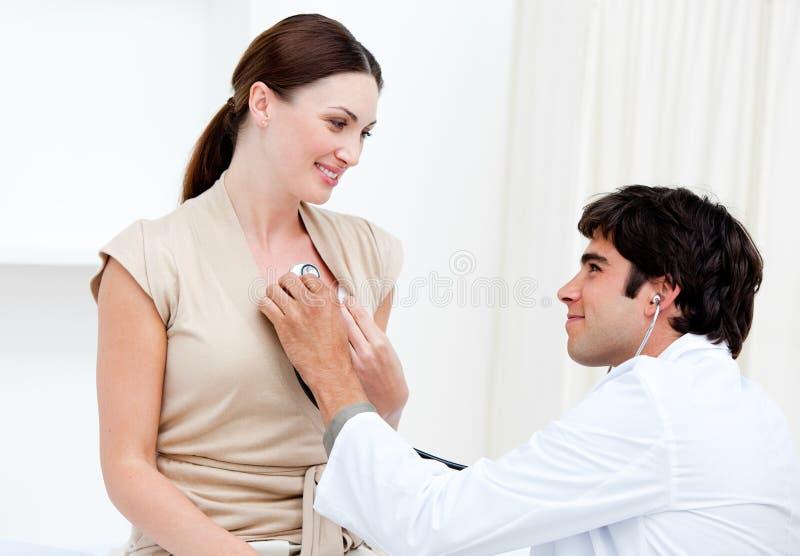 Doctor de sexo masculino que examina a un paciente femenino imágenes de archivo libres de regalías