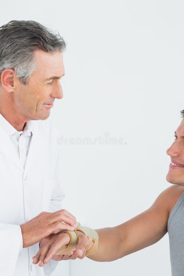 Doctor de sexo masculino que examina una mano de los pacientes en la oficina médica fotos de archivo libres de regalías