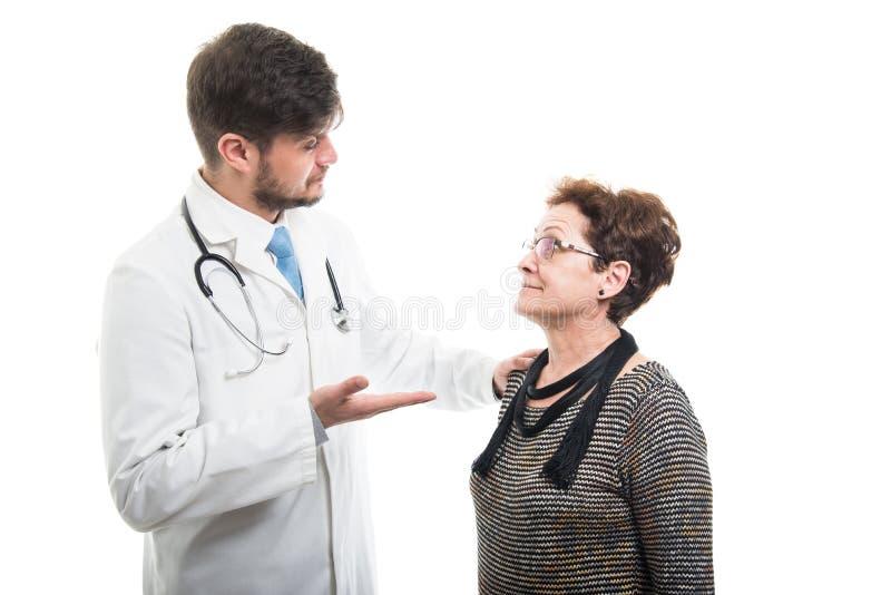 Doctor de sexo masculino que explica algo al paciente mayor femenino fotos de archivo