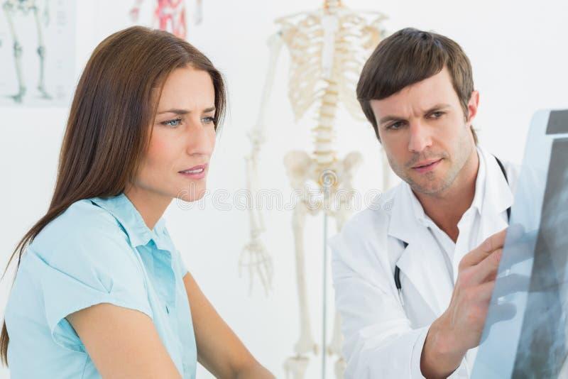 Doctor de sexo masculino que explica la radiografía de la espina dorsal al paciente femenino fotos de archivo