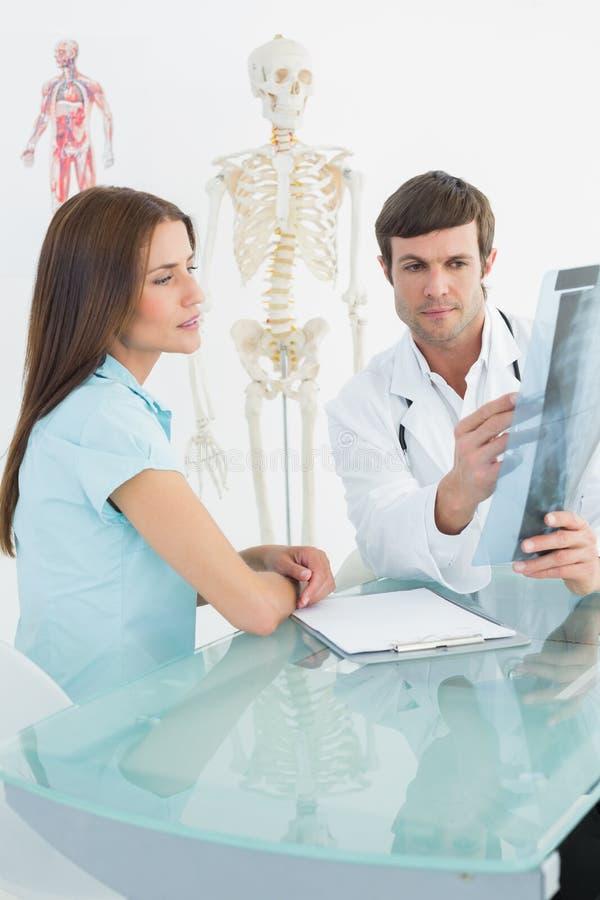 Doctor de sexo masculino que explica la radiografía de la espina dorsal al paciente femenino imagenes de archivo