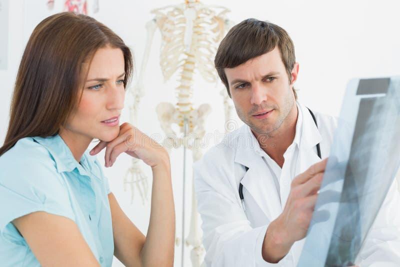 Doctor de sexo masculino que explica la radiografía de la espina dorsal al paciente femenino fotos de archivo libres de regalías