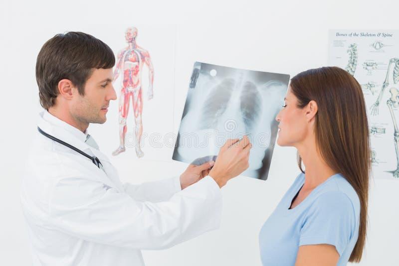 Doctor de sexo masculino que explica la radiografía de los pulmones al paciente femenino foto de archivo