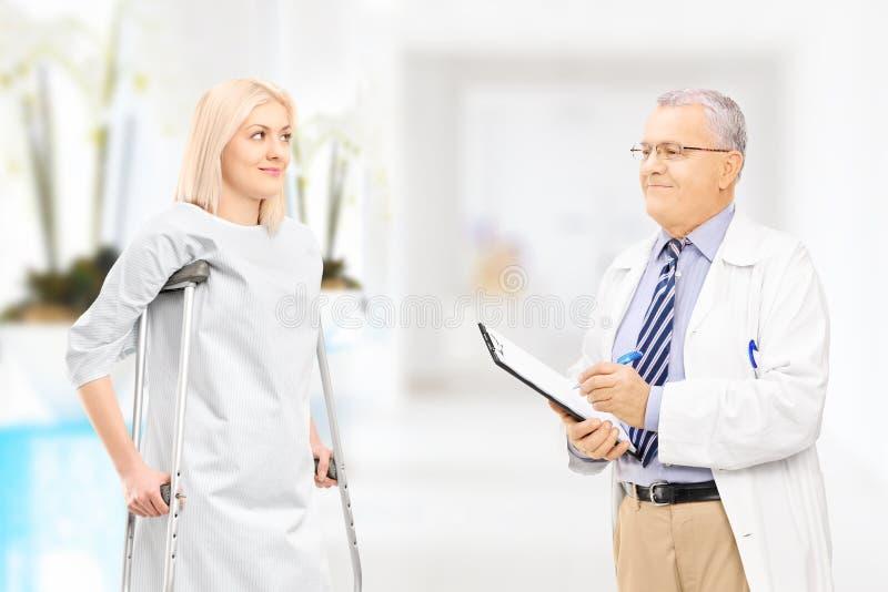 Doctor de sexo masculino que habla con el paciente femenino con las muletas en hospital foto de archivo libre de regalías