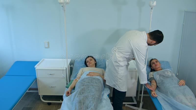 Doctor de sexo masculino que habla con los pacientes femeninos en el goteo que descansa en sala de hospital fotos de archivo