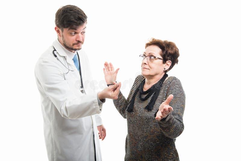 Doctor de sexo masculino que hace gesto del efectivo al paciente mayor femenino fotografía de archivo libre de regalías